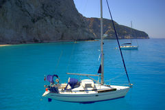 Sailing holidays in blue bay. Yachts in aquamarine clear water of the Ionian sea, nearby the coast of the Greek island Lefkada in Porto Katsiki beach Royalty Free Stock Image