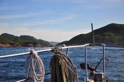 Sailing into the horizon, Sai Kung, Hong Kong. Bow of ship with ropes tied to railings, sailing on a clear day in Sai Kung, Hong Kong Stock Photos