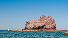 Sailing by the Island. A sailboat explores an offshore island made of stone and the rocky coastline Stock Photos