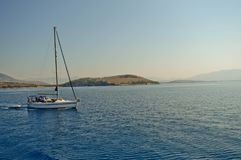 Sailing between islands on the Ionian Sea. A small sailing-boat with some tourists on the greek seas Royalty Free Stock Images