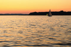 Sailboat on lake by golden sunset Stock Photography