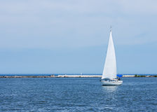 Sailing On Lake Erie. A small white single mast sailboat cruises inside the breakwall that protects the harbor at Cleveland, Ohio from the large waves sometimes royalty free stock images