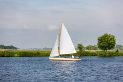 Sailing on the lake `t Joppe in the Netherlands. A sailboat with 3 men sailing on the lake `t Joppe in the Netherlands stock photo