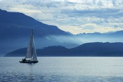 Sailing on lake Zug. In Switzerland with the Alps in the background Stock Image