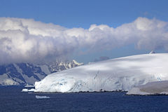 Sailing through the Lemaire Channel, Antarctica. Sailing through the Lemaire Channel. Snow covered mountains, rolling clouds & a beautiful blue sky. Antarctica stock image