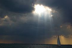 Sailing into the light. Sloop on lake st. clair sailing toward port away from an afternoon rainshower some miles south Stock Photography