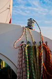 Sailing Lines. Several lines or ropes coiled and tied to a sail boat.  There is one line that is wrapped around the winch and a red and white sail is set and Royalty Free Stock Images