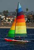 Sailing in Mission Bay. A young woman is sailing in Mission Bay, San Diego. A colorful yacht with rainbow-colored sail stands out against a background of out-of Stock Photography