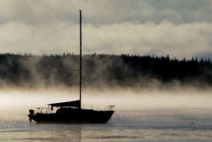 Sailing into the Mist. Silhouette of a sailboat in the morning mist Royalty Free Stock Image