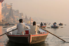 Sailing on a misty day. Ganges river. People coming and going by boat on the early morning in Varanasi, India Royalty Free Stock Photography