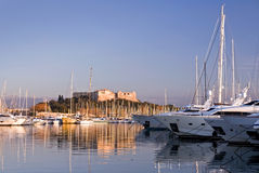 Sailing and motor yachts in Antibes. Sailing and motor yachts moored in Antibes (France) with old fortress on background Stock Images