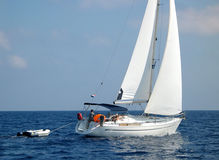 Sailboat sailing with dinghy. Side view of sailboat sailing with dinghy stock photos