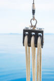 Sailing pulley. Closeup of sailing pulley with clear sky and sea in the background Stock Photo