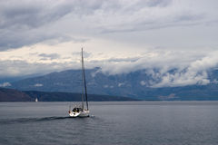 Sailing in raining day. A boat is sailing in a sea. Stormy clouds on the back stock images