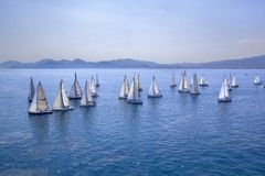Sailing regatta or a group of small water racing boats in the Mediterranean, a panoramic view with blue mountains on a horizon Royalty Free Stock Photography