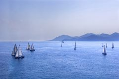 Sailing regatta or a group of small water racing boats in the Mediterranean, a panoramic view with blue mountains on a horizon Stock Image