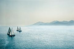 Sailing regatta or a group of small water racing boats in the Mediterranean, a panoramic view with blue mountains on a horizon Royalty Free Stock Photo