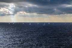 Sailing regatta in the open sea. Manoeuvres of sailing yachts in the open sea against the background of rays of light breaking through storm clouds Royalty Free Stock Image
