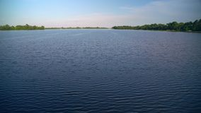 Huge water flow of calm lake. Sailing on the river. Blue water and clear blue sky merge on the horizon stock video