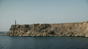 Sailing by a rocky cliffs with lighthouse at tourist resort in Egypt. Tourist resort in Egypt, traveling on the sea, sightseeing animals and sunken ships stock footage