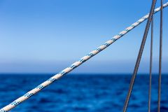 Sailing Ropes in Front of bight blue Ocean and Sky Background.  royalty free stock photo