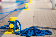 Sailing ropes tied around pins in sunlight Stock Image