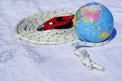 Sailing round the world. Globe and sailing tackle on top of a maritime chart royalty free stock photography