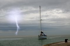 Sailing in the sea. Sailing near the port with lightning at horizon Royalty Free Stock Photo