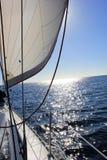 Sailing on the sea. Under white sails hoisted towards the sun Stock Image