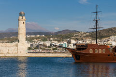 Sailing ship on the background of a lighthouse in Greece Stock Image