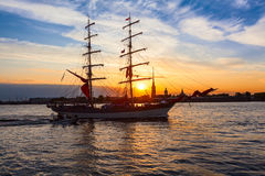 Sailing ship on the background of Peter and Paul fortress in the rays of the setting sun Stock Photos