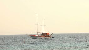 Sailing ship floats in the sea, sailing yacht, sea walk on a sailing yacht, Silhouette of solitary yacht without sails. Sailing ship floats in the sea, sailing stock footage