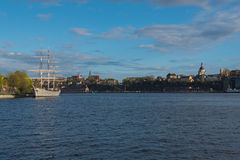 Sailing ship is in foreground of Skeppsholmen islands at evening Royalty Free Stock Photos