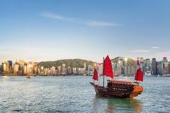Sailing ship and the Hong Kong Island skyline at evening Royalty Free Stock Image