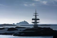 Sailing ship among the icebergs Stock Photos