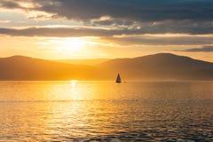 Sailing ship on the lake. At sunset skyline royalty free stock image