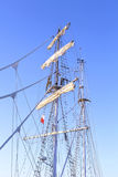 Sailing ship mast against a clear blue sky. Stock Photo