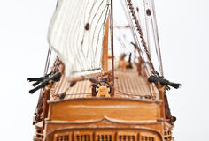 Sailing ship model. Rear view of sail ship model with steering wheel and cannons royalty free stock photo