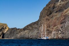 A sailing ship moored against the cliffs of Isabela Island, Galapagos Islands, Ecuador royalty free stock photos