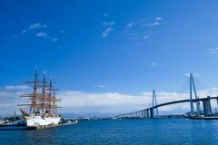 Sailing ship named Kaiomaru and bridge in Japan. Pictured sailing ship named Kaiomaru and bridge in Japan Stock Photo