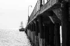Sailing ship near the pier. Black and white photo. Royalty Free Stock Photo