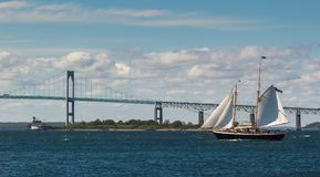 Sailing Ship, Newport Bridge, and Rose Island Lighthouse. A view of a two-master yacht sailing in front of the Newport Bridge and Rose Island Lighthouse, Rhode stock photos