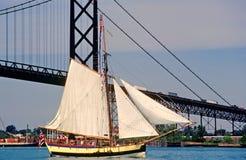 Sailing Ship on a river passing a bridge. A antique sailing ship making its way past a bridge down a river Royalty Free Stock Photos