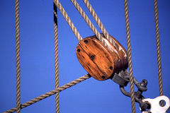 Sailing ship ropes and pulley. Old Sailing ship ropes and pulley. block and tackle with blue sky as back ground Royalty Free Stock Photography