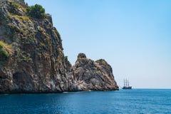 A sailing ship sails along the Mediterranean coast Stock Image