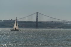 A sailing ship sails through the waters of the Tejo River on the coasts of the city of Lisbon. In the distance you can see the famous bridge of April 25th royalty free stock image