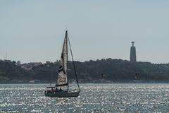 A sailing ship sails through the waters of the Tejo River on the coasts of the city of Lisbon. In the distance you can see the population of Almada and a stock images