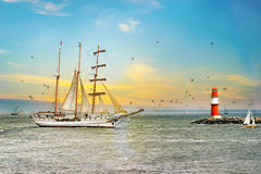 Sailing ship on the sea at sunset. Lighthouse and birds. Sailing ship on the sea at beautiful sunset. Lighthouse and birds. Tall Ship.Yachting and Sailing Royalty Free Stock Photography