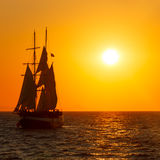 Sailing ship silhouette in sunset on the sea Stock Photos