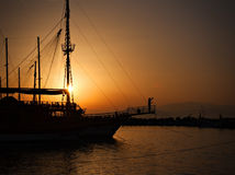Sailing ship silhouetted against amber sky Stock Image